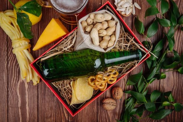Вид сверху бутылка пива с арахисом в мешочке с картофельными чипсами и мини-кренделями на соломе в красной коробке и кружка пива с сыром и лимоном на деревенском Бесплатные Фотографии