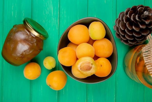 Вид сверху миску абрикосов и банку персикового джема с компотом и шишка на зеленом фоне Бесплатные Фотографии