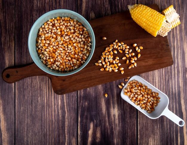 トウモロコシ種子のボウルの平面図は、木のトウモロコシ種子のスプーンでまな板の上にトウモロコシをカット 無料写真