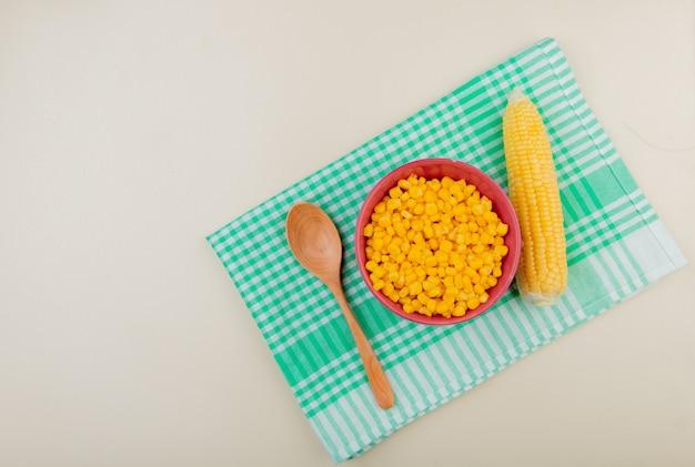 布の上にスプーンとトウモロコシのトウモロコシ種子のボウルとコピースペースを持つ白のトップビュー 無料写真