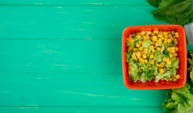 右側にスライスしたレタスとほうれん草の全体レタス、コピースペース付きのgreと黄色のエンドウ豆のボウルの平面図 無料写真