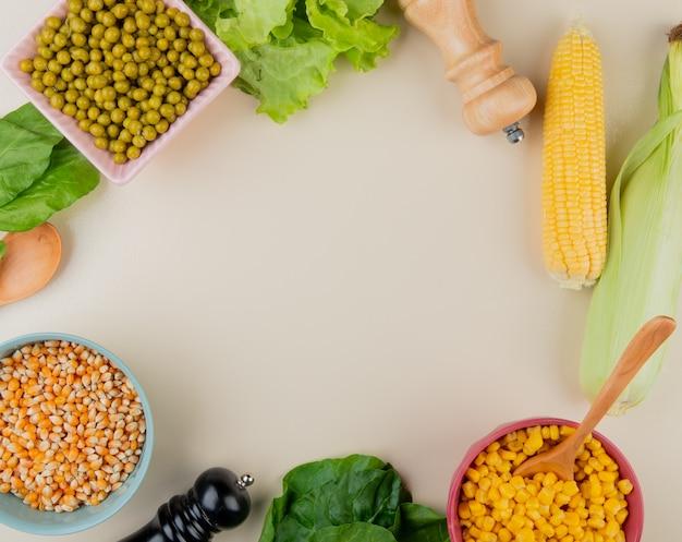 コピースペースと白のボウルに乾燥および調理されたトウモロコシ種子グリーンピースレタスほうれん草のトウモロコシの穂軸の平面図 無料写真