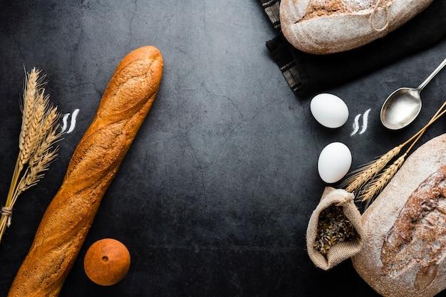 黒の背景にパンや食材のトップビュー 無料写真