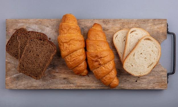 灰色の背景のまな板にクロワッサンスライスライ麦とバゲットとしてパンの上面図 無料写真