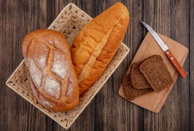 バスケットの無愛想なベトナムのバゲットとしてのパンと木製の背景のまな板にナイフでスライスしたライ麦パンの上面図 無料写真