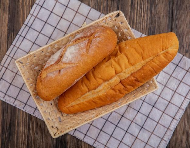 木製の背景に格子縞の布の上のバスケットの無愛想なベトナムのバゲットとしてのパンの上面図 無料写真