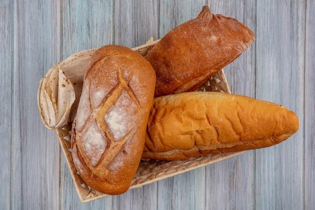 木製の背景にバスケットの無愛想なフラットブレッドとバゲットとしてパンの上面図 無料写真