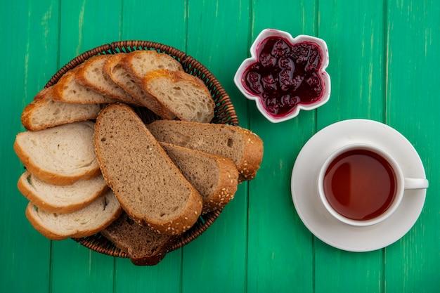 バスケットに茶色の穂軸とバゲットのスライス、ボウルにラズベリージャム、緑の背景にお茶を入れたパンの上面図 無料写真