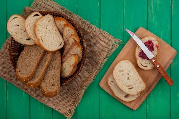 緑の背景のまな板にナイフでラズベリージャムを塗った荒布とパンのスライスのバスケットに種をまく茶色の穂軸とバゲットスライスとしてのパンの上面図 無料写真
