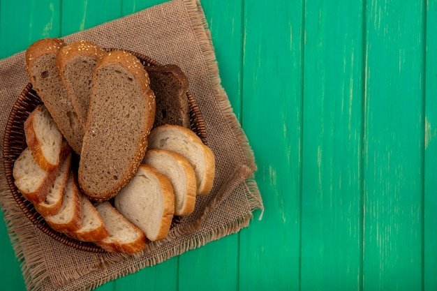 コピースペースと緑の背景の荒布のバスケットに種をまく茶色の穂軸とバゲットスライスとしてパンの上面図 無料写真