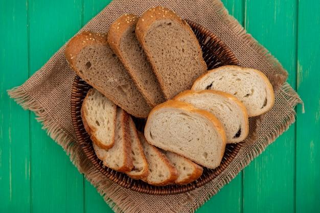 緑の背景の荒布のバスケットに種をまく茶色の穂軸とバゲットスライスとしてパンの上面図 無料写真