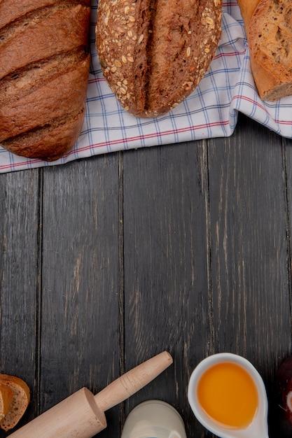 シードベトナムバゲットとコピースペースを持つ木製の背景にバター麺棒ミルクを布に黒いパンとしてパンのトップビュー 無料写真