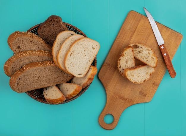スライスされたバゲットシード茶色の穂軸とライ麦のものとしてバスケットと青い背景のナイフでまな板にパンの上面図 無料写真