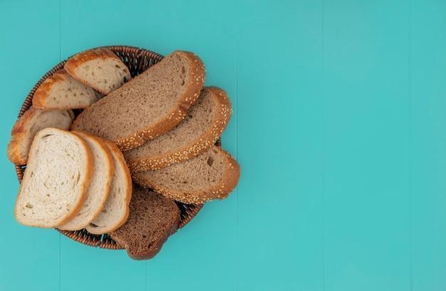 スライスされたバゲットシード茶色の穂軸とコピースペースと青い背景のバスケットにライ麦のものとしてパンの上面図 無料写真