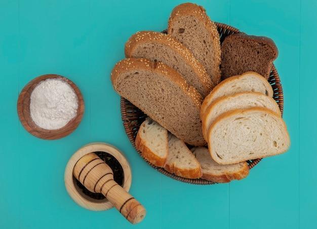 スライスしたバゲットシード茶色の穂軸と青い背景に小麦粉と黒コショウとバスケットのライ麦のものとしてパンの上面図 無料写真