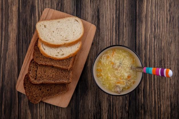 まな板と木製の背景にスプーンでチキンオルゾースープのボウルにスライスしたライ麦と白いものとしてパンの上面図 無料写真