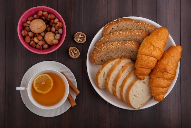 Вид сверху на хлеб в виде нарезанного семенами багета из коричневого початка и круассанов в тарелке и миске с орехами грецкими орехами и чашкой горячего пунша с корицей на блюдце на деревянном фоне Бесплатные Фотографии