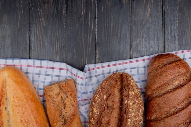 ベトナムのフレンチシードバゲットと黒のパンと格子縞の布とコピースペースを持つ木製の背景としてパンのトップビュー 無料写真