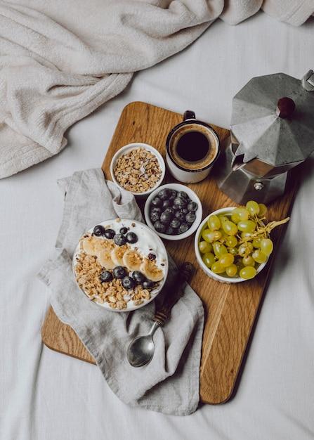 Вид сверху на завтрак в постели с хлопьями и кофе Premium Фотографии