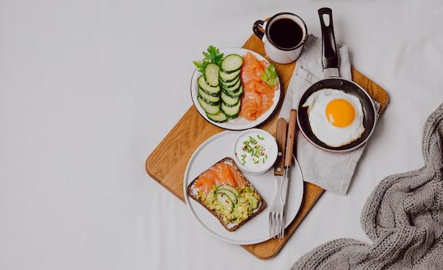 Вид сверху бутербродов для завтрака на кровати с жареным яйцом и копией пространства Бесплатные Фотографии