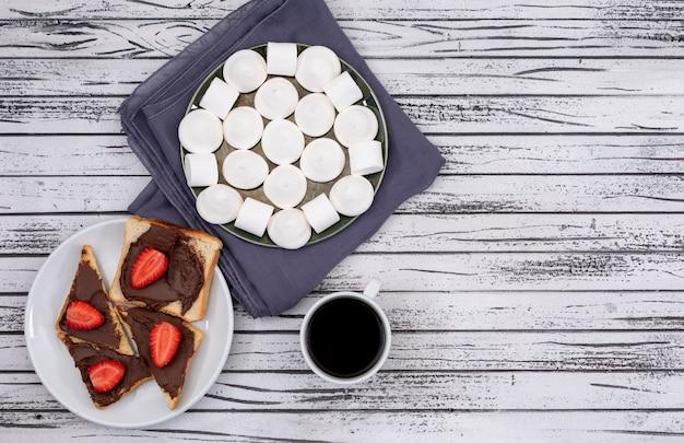 Вид сверху завтрак тосты с шоколадом и клубникой, зефиром и кофе на белой деревянной поверхности горизонтальной Бесплатные Фотографии