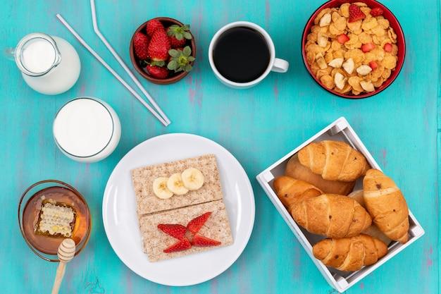 青い表面の水平にクロワッサン、コーンフレーク、果物、牛乳、蜂蜜と朝食の平面図 無料写真