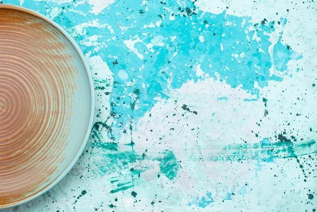 Вид сверху коричневой тарелки пустой на голубом, тарелке еды Бесплатные Фотографии
