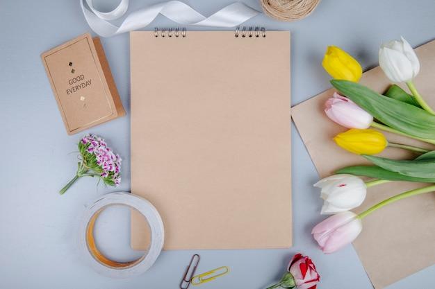 Взгляд сверху коричневого листа бумаги с открыткой и красочными цветками тюльпана с турецкой гвоздикой и розой на голубой предпосылке Бесплатные Фотографии