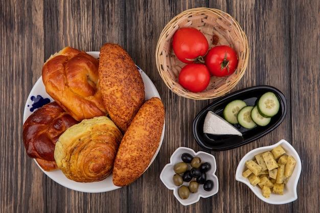 木製の背景のボウルにオリーブとバケツに新鮮なトマトとプレート上のパンの上面図 無料写真