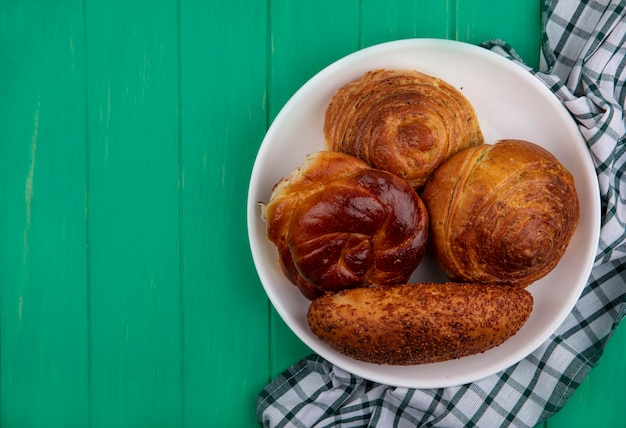 コピースペースと緑の木製の背景にチェックの布の上の白いプレート上のパンの上面図 無料写真