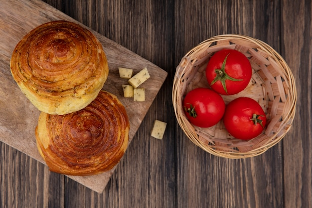 木製の背景のバケツにチーズとトマトのスライスを刻んだ木製のキッチンボード上のパンの上面図 無料写真