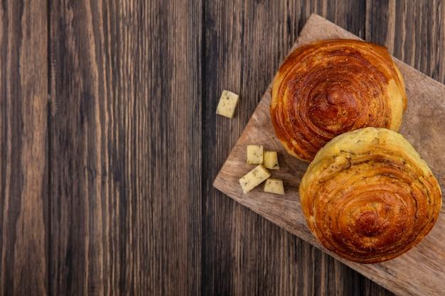 コピースペースのある木製の背景にチーズのスライスを刻んだ木製のキッチンボード上のパンの上面図 無料写真