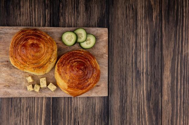 コピースペースのある木製の背景にきゅうりとチーズのスライスを刻んだ木製のキッチンボード上のパンの上面図 無料写真