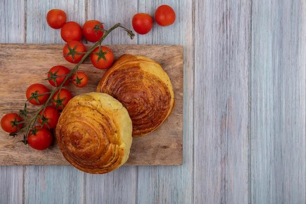 コピースペースと灰色の木製の背景に新鮮なブドウのトマトと木製のキッチンボード上のパンの上面図 無料写真