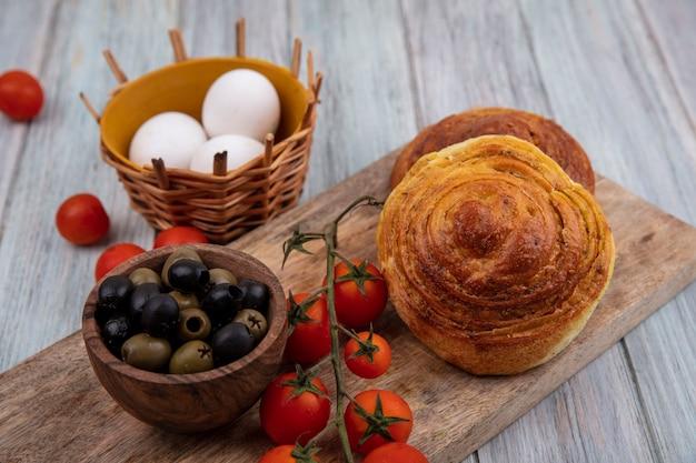 木製のボウルにオリーブと灰色の木製の背景の上のバケツに卵と新鮮なブドウのトマトと木製のキッチンボード上のパンの上面図 無料写真