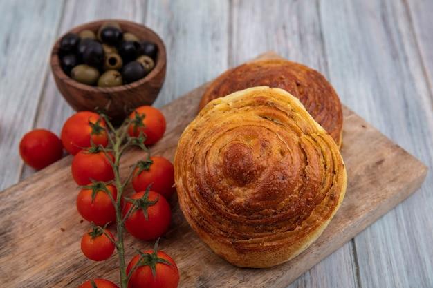 灰色の木製の背景の上の木製のボウルにオリーブとオリーブと新鮮なブドウのトマトと木製のキッチンボード上のパンの上面図 無料写真