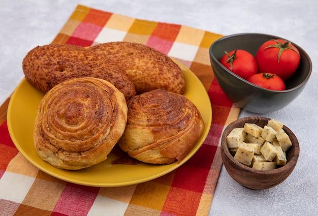 白い背景の上のボウルにトマトと木製のボウルにチーズとチェックの布の上の黄色いプレート上のパンの上面図 無料写真