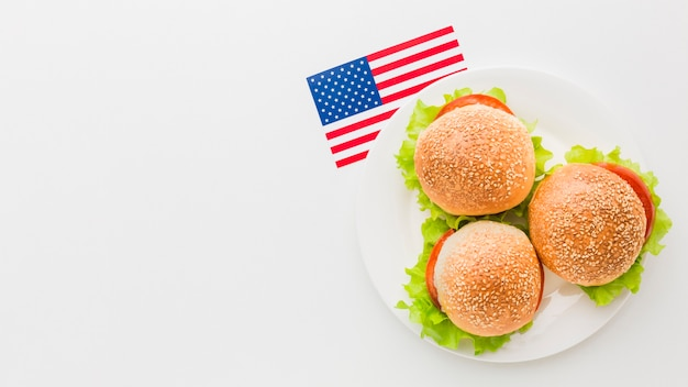Взгляд сверху бургеров на плите с космосом экземпляра и американским флагом Бесплатные Фотографии