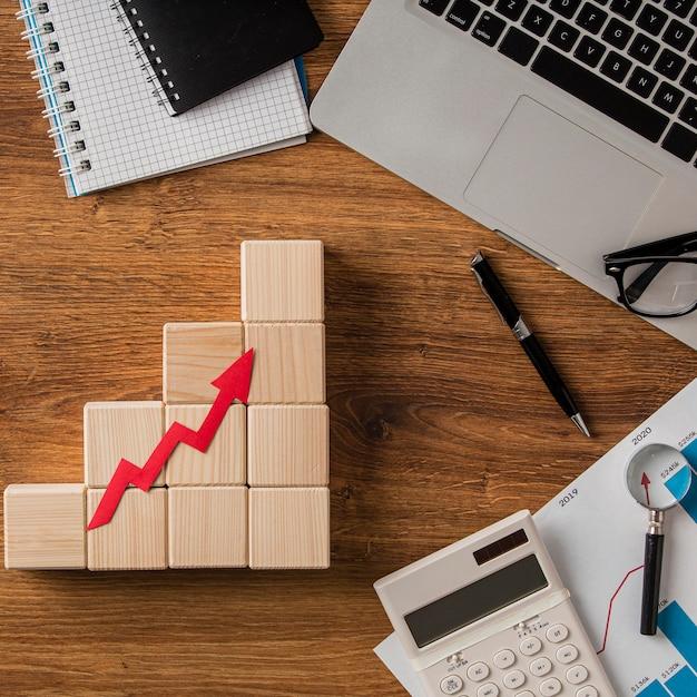 ビジネスアイテムと木製ブロックの成長矢印の上面図 Premium写真