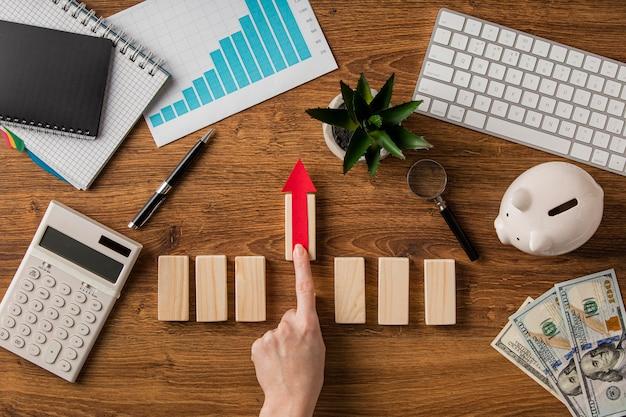 成長チャートと木製ブロックを押し上げる手でビジネスアイテムの上面図 Premium写真