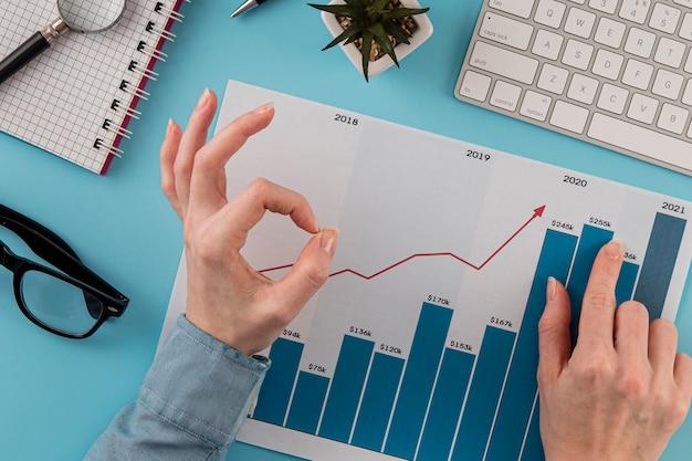 Вид сверху на бизнес-элементы с диаграммой роста и руками, дающими хороший знак Бесплатные Фотографии