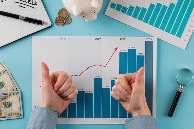 Вид сверху на бизнес-элементы с диаграммой роста и руками, поднимающими пальцы вверх Бесплатные Фотографии