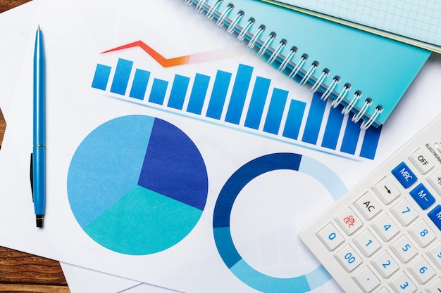 계산기와 나무 테이블에 비즈니스 종이 그래프의 상위 뷰 프리미엄 사진