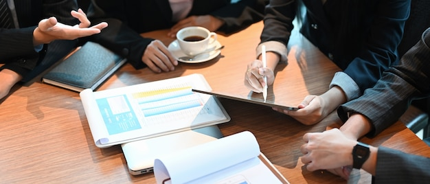 Вид сверху деловых людей работает с планшетным компьютером и оформляет документы за деревянным рабочим столом. Premium Фотографии