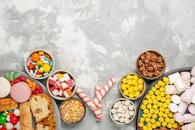 白い壁にフランスのマカロンベーグルとキャンディーとケーキのスライスの上面図 無料写真