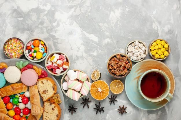흰색 테이블에 차 한잔과 함께 마카롱, 베이글, 사탕과 케이크 조각의 상위 뷰 무료 사진