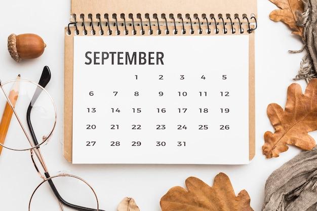 Вид сверху календаря с осенними листьями и очки Premium Фотографии