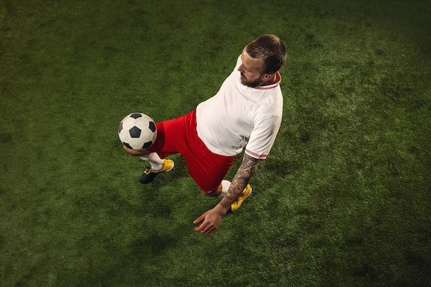 草の緑の背景に白人サッカー選手またはサッカー選手の上面図。若い男性のスポーツモデルのトレーニング、練習。ボールを蹴る、攻撃する、捕まえる。スポーツ、競争、勝利の概念。 無料写真