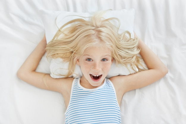ブロンドの髪、そばかす、青い目をした陽気な少女の平面図、白い枕とリネンの上に横たわるストリップされたパジャマを着て、楽しんで笑って、昼間の昼寝をしたくない 無料写真