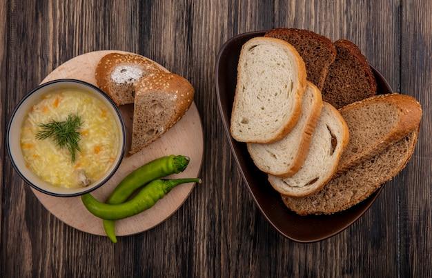 ボウルに鶏肉のオルゾスープとまな板の上の唐辛子、木製の背景にボウルに茶色の穂軸白とライ麦パンのスライスをシードした上面図 無料写真